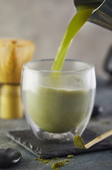Matcha tea is poured into a glass from a silver jug