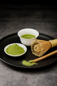 Matcha tea on plate with bamboo whisk