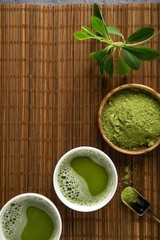 Порошок чая матча и аксессуары для чая на фоне бамбуковой салфетки. чайная церемония. здоровый напиток. традиционный японский напиток.