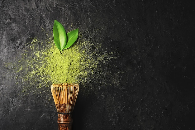 Matcha tea powder on dark background with whisk and leaves with copy space.