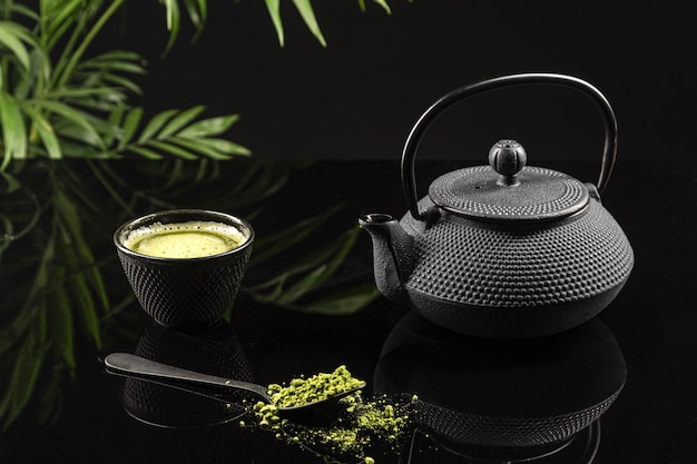 Matcha tea powder and tea accessories on black background. tea ceremony. traditional japanese drink.