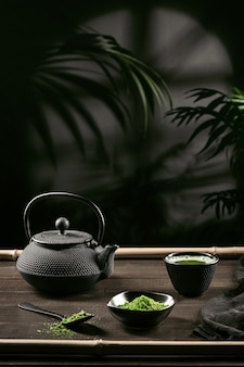 Matcha tea powder and tea accessories on dark wooden base. tea ceremony. traditional japanese drink. vertical format.