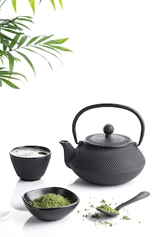 Matcha tea powder and tea accessories on white base with copyspace. tea ceremony. traditional japanese drink vertical format.
