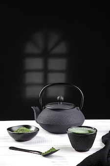 Matcha tea powder and tea accessories on white wooden base .traditional japanese drink. vertical format.