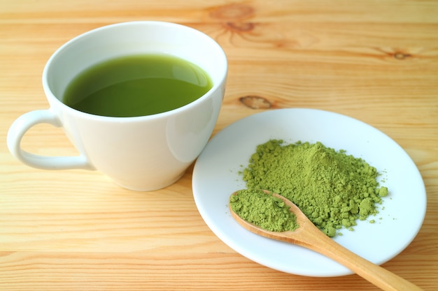 Matcha tea powder with a wooden spoon and a cup of hot matcha green tea on the wooden table