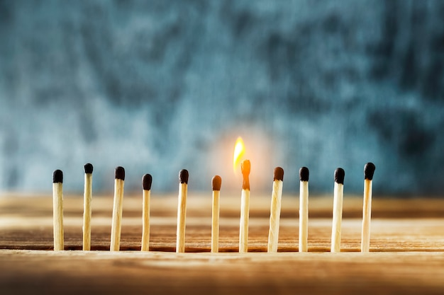 Matches stand in a row, one match burns.