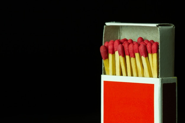 Matches stick in red paper box on black
