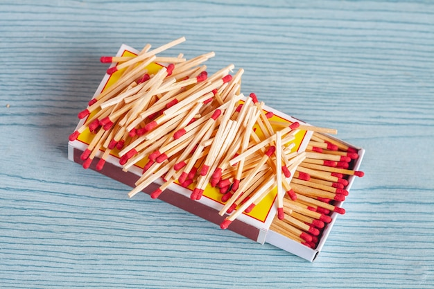 Matchstick out of matchbox on color wood table.