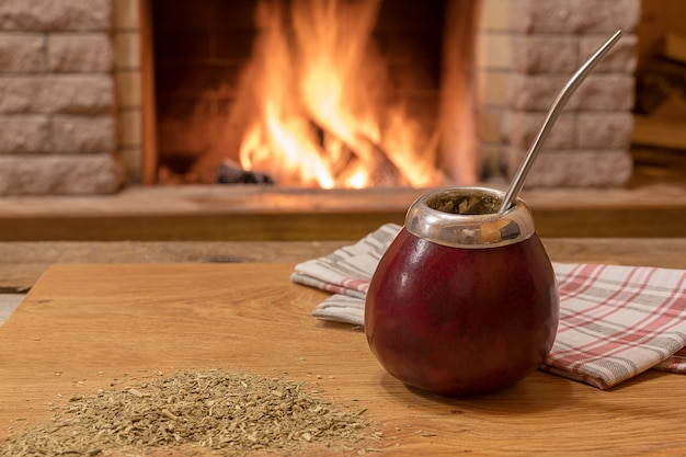 Mate drinking , near cozy fireplace, in country house.