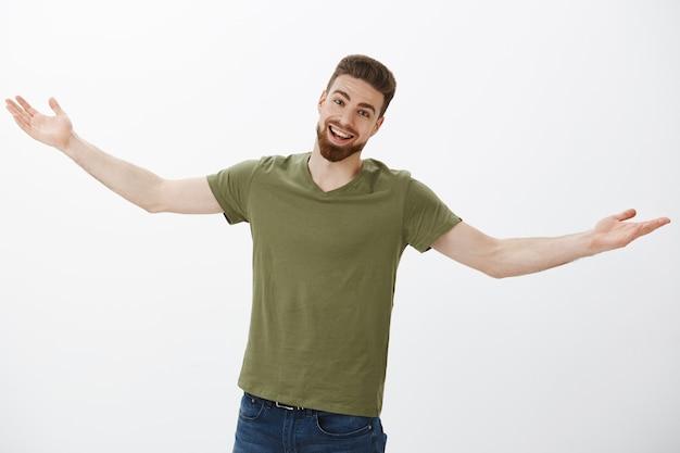 Приятель, давно не виделись, обними меня. портрет удивленного и счастливого возбужденного симпатичного кавказского мужчины с бородой, дружелюбно улыбающегося с довольным выражением лица, протягивающего руки в знак приветствия и приветствия