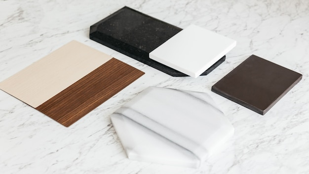 Material sample selections including granite tile, marble tile, acoustic tile, walnut and ash wood laminate with plant on marble top table.