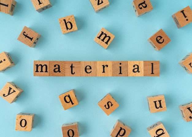 Material word on wooden block. flat lay view on blue background.