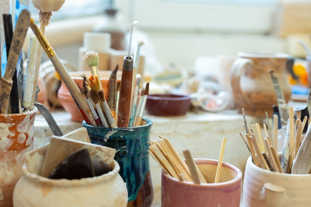 Materials being organized. pile of paintbrushes staying with special wooden and metal tools and being covered in clay