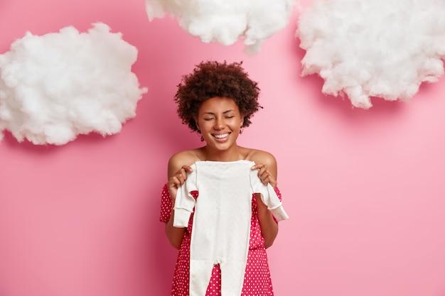 マタニティと期待の概念。幸せな未来の母親は、希望の赤ちゃんを待ち、子供服でポーズをとり、前向きに笑い、目を閉じ、素晴らしいニュースで夫を驚かせます
