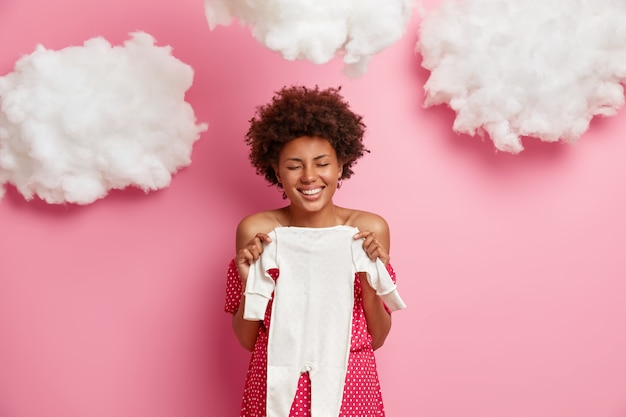 Maternity and anticipation concept. happy future mother waits for desired baby, poses with child clothes, giggles positively and closes eyes, going to make surprise for husband with awesome news