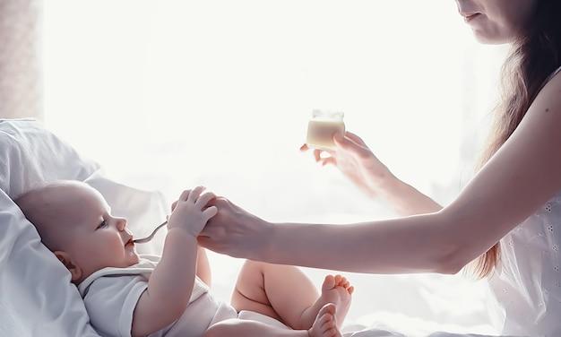 Концепция материнства. молодая мама кормит своего малыша. первая прикорм и кормление грудью. большая семья в белых одеждах.