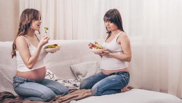 Концепция материнства, две беременные женщины едят свежий салат в домашних условиях