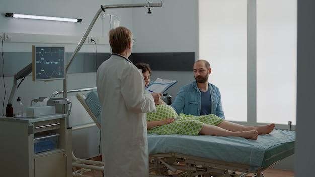 病棟に座っている妊婦さんとご主人にアドバイスをする産科医。クリニックで出産の専門家から医療の親の援助を受けている若い白人カップル