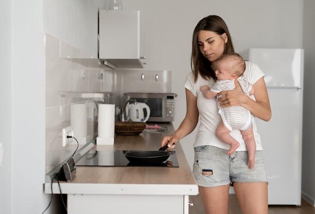 産休。幼い息子と夕食を準備する若い母親、キッチンのインテリア、空きスペース