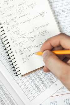 Math formulas are written in pencil in a notebook holding a man in hands, math problems