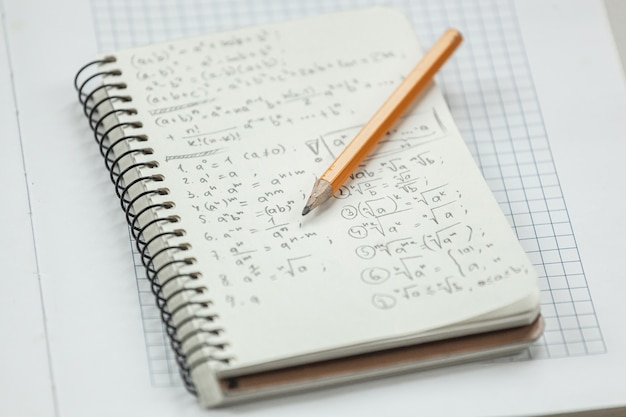 Math formulas are written in pencil on piece of paper, math problems