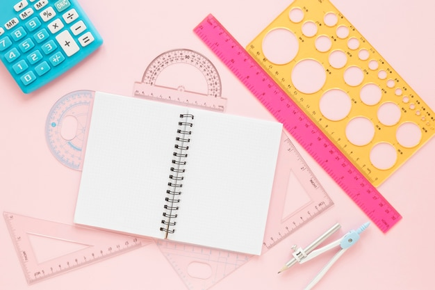 Math rulers supplies with open empty notebook flat lay