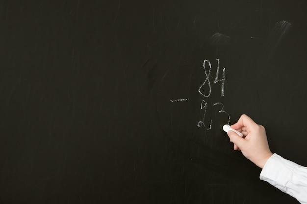 Учитель математики в русской школе пишет мелом задание на вычитание по столбцу на доске