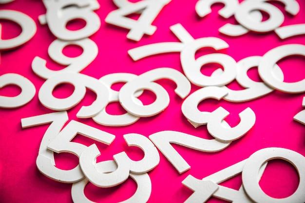 ボード上の固体の数字で作られた数学の背景。ピンクで隔離