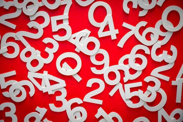 ボード上の固体の数字で作られた数学の背景。上面図、赤で隔離