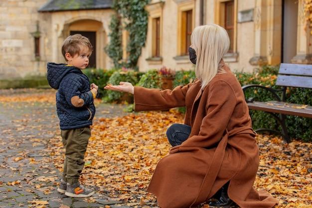 Мать и сын играют в парке осенью