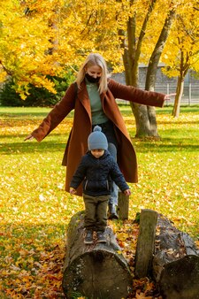 Mather and son are playing in the park in autumn
