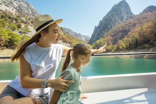 Мать с маленькой дочерью на экскурсионном корабле или лодке, наслаждаясь озером во время летних каникул. концепция праздника путешествий и туров.