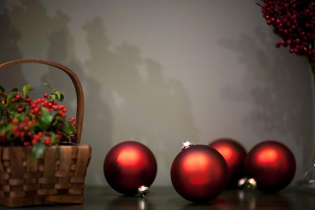 ベリーと枝が付いている籐のバスケットの近くの赤い色のマットと光沢のあるクリスマスツリーのおもちゃ