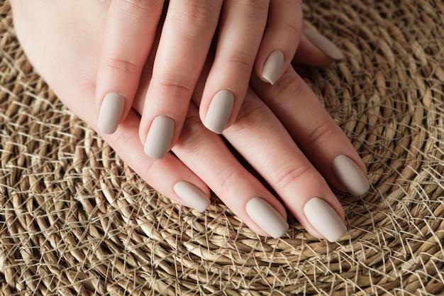 Матовые обнаженные бежевые ногти крупным планом. зимний или осенний маникюр на руке женщины