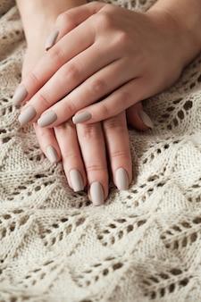 Матовые обнаженные бежевые ногти крупным планом. зимний или осенний маникюр, женская рука на теплом свитере