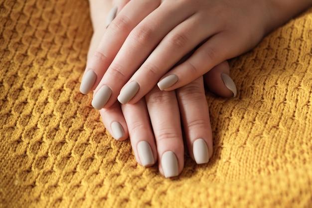 Матовые обнаженные бежевые ногти крупным планом. зимний или осенний маникюр, женская рука на теплом желтом свитере