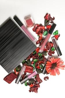 Набор матовой помады, палитра теней и сухие цветы на белом фоне