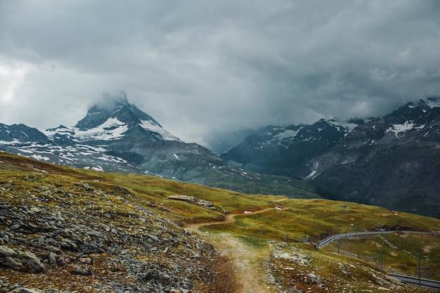 Маттерхорн в облаках горная тропа трава камни церматт швейцарские альпы приключение в швейцарии