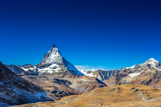 Matterhorn peak mountain in summer with clear blue sky and day moon at zermatt