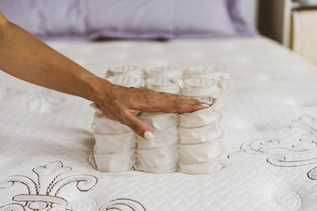 Материал матраса в руках женщины