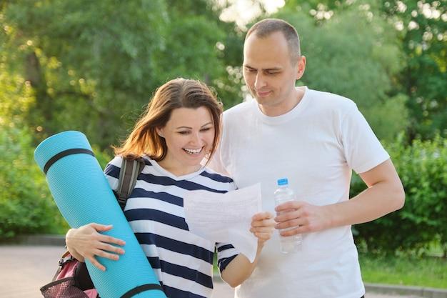 건강한 라이프 스타일을위한 야외 성숙한 활동적인 커플, 웃는 여자와 남자가 종이 편지를 읽고, 기쁨의 행복의 감정