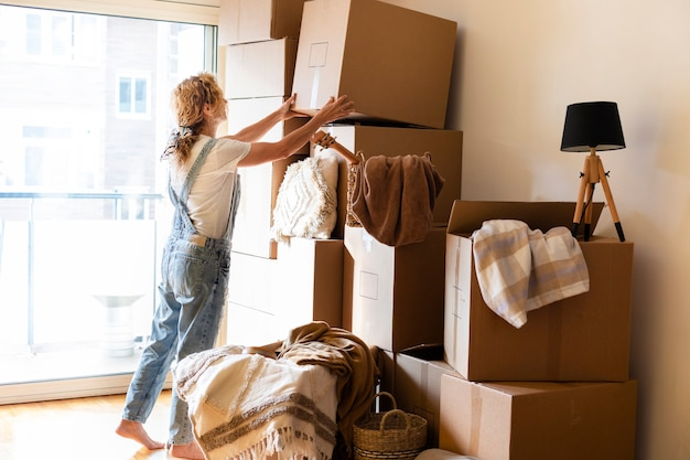Mature adult blonde caucasian woman put cardboard box in a pile. copy space. moving in concept.