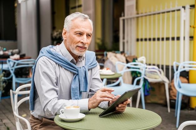 성숙한 성인 바에서 자신의 태블릿을 사용하여