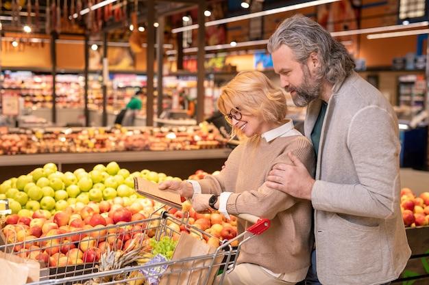 Зрелая ласковая пара в повседневной одежде смотрит на страницу блокнота со списком покупок во время движения по современному гипермаркету