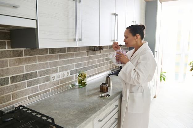 白いワッフルバスローブを着た成熟したアフリカ系アメリカ人の女性は、キッチンに立って間欠泉のコーヒーメーカーでそれを準備しながらコーヒーの香りを楽しんでいます