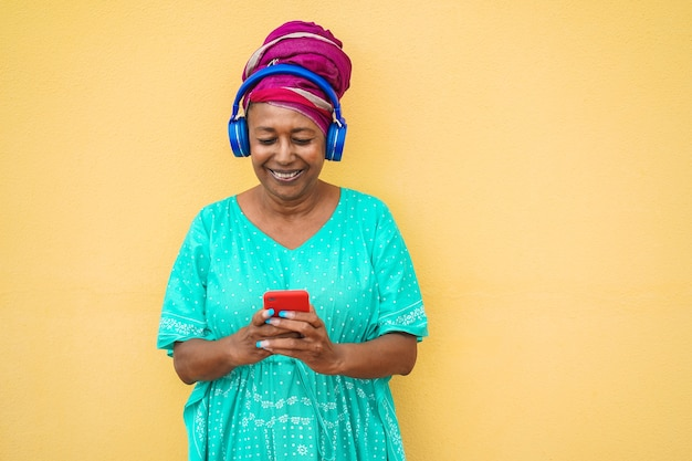 Mature african woman using smartphone app for creating playlist music - senior female having fun with mobile phone technology - tech and joyful elderly lifestyle concept - focus on face