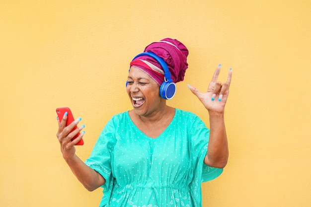 Mature african woman using smartphone app for creating playlist with rock music - senior female having fun with mobile phone technology - tech and joyful elderly lifestyle concept