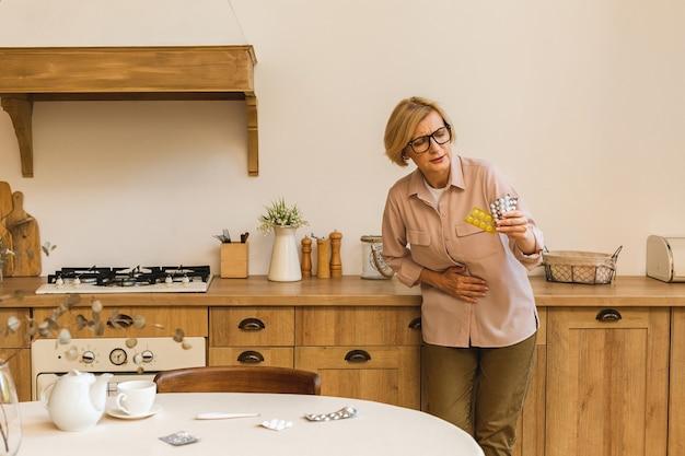 自宅のキッチンで丸薬と水ぶくれを保持している成熟した高齢の年配の女性。気分が悪い。