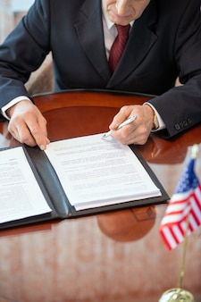 Зрелый американский делегат в строгой одежде, склонившись над столом, просматривая условия договора о деловом партнерстве