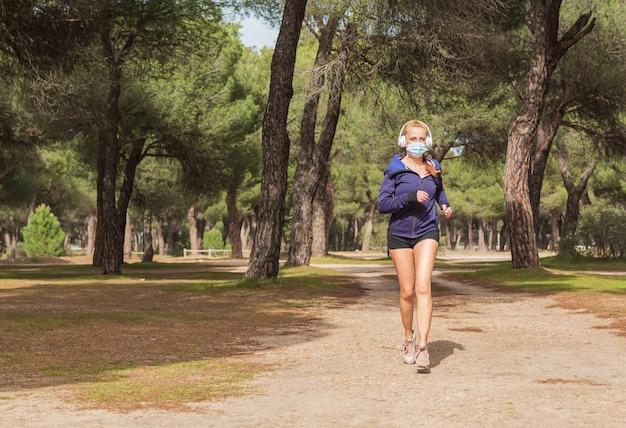 公共の都市公園で一人で走ったりジョギングしたりする体調の良い成熟したフィットの女性。ウイルスやアレルギー感染から身を守るために保護マスクを着用してください。健康的なライフスタイルのコンセプト。